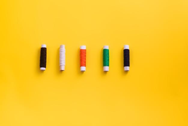 Катушки с нитками разных цветов и размеров на ярком, красочном фоне. плоская планировка