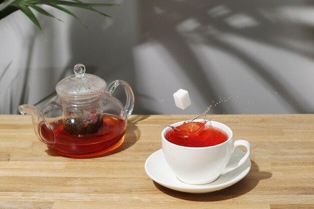 木製のテーブルでフルーツティーを参照してください。カップに落ちる砂糖の立方体。お茶のスプラッシュ。フルーツティーの急須。