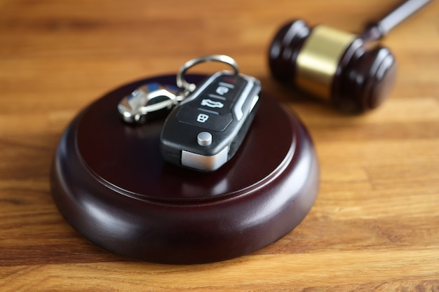 Referee gavel and remote control from car on table car seizure by court concept