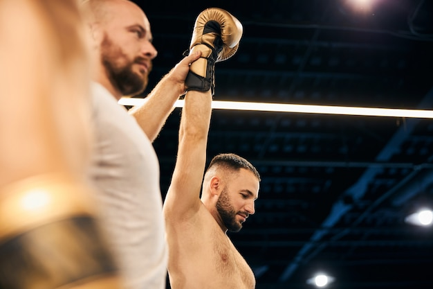 A referee holding in the air the hand of a sparring winner