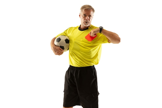 Referee holding ball and showing a red card to a football or soccer player while gaming on white wall. concept of sport, rules violation, controversial issues, obstacles overcoming.