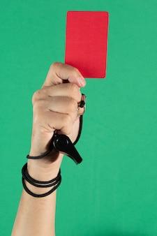 赤いカードを持っている審判の手と緑の背景に笛を吹く。