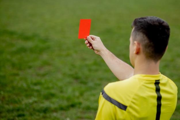 게임하는 동안 불쾌한 축구 또는 축구 선수에게 레드 카드를 보여주는 심판. 스포츠의 개념, 규칙 위반, 논란의 여지가있는 문제, 극복하는 장애물.