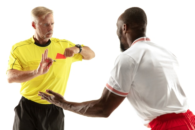 Referee showing a red card to a displeased african-american football or soccer player while gaming isolated on white wall. concept of sport, rules violation, controversial issues, emotions.