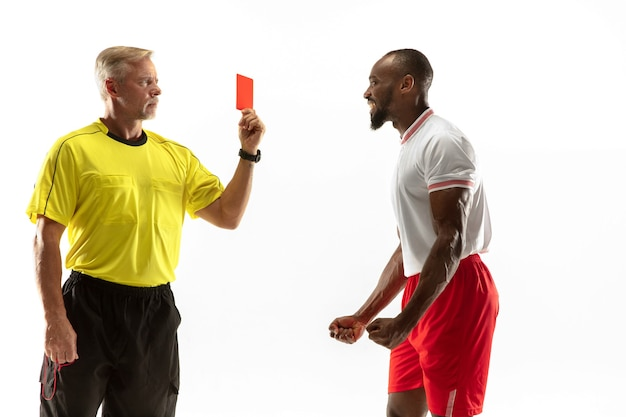 Referee showing a red card to a displeased african-american football or soccer player while gaming isolated on white wall.