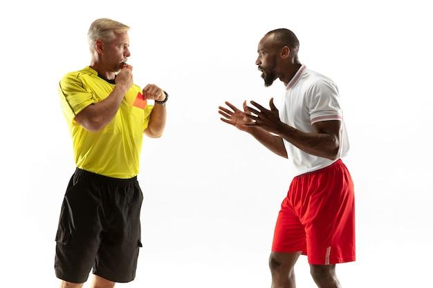 Arbitro che mostra un cartellino rosso a un giocatore di football o di calcio afroamericano dispiaciuto