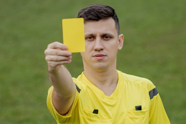 Referee showing a red card to a displeased football or soccer player while gaming. concept of sport, rules violation, controversial issues, obstacles overcoming.