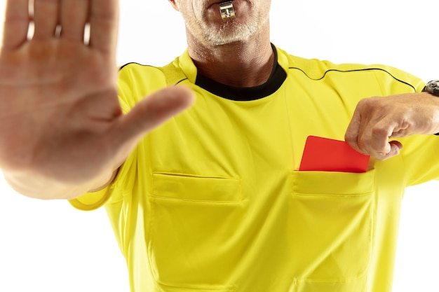 Referee showing a red card to a displeased football or soccer player while gaming isolated on white wall. concept of sport, rules violation, controversial issues, obstacles overcoming.