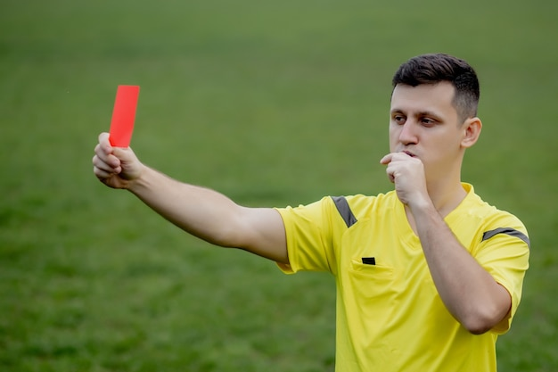 Referee showing a red card to a displeased football or soccer player while gaming
