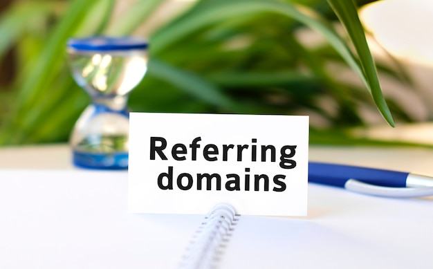 Referring domains - text on a notebook with a spring and a gray handle