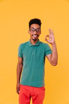 大丈夫サインでポーズをとって赤いズボンで洗練されたアフリカの少年。立っている大きな流行のメガネの前向きな男。