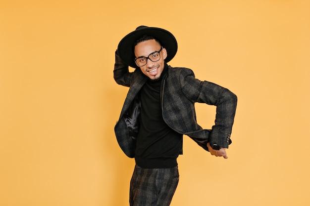 写真撮影中に楽しんでいる洗練されたアフリカ人。黄色の壁に踊る帽子と眼鏡の背の高い黒人の男の笑顔の屋内写真。