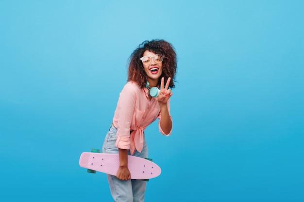 Donna nera raffinata in grandi cuffie che tiene lonboard e che mostra il segno di pace. ragazza mulatta felice in camicia rosa alla moda che ride in camera con interni blu dopo il pattinaggio.