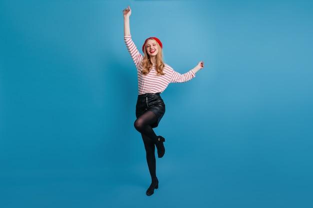Утонченная блондинка танцует и машет руками. великолепная французская женщина позирует на синей стене.