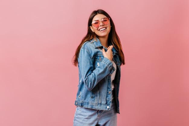 Raffinata ragazza bruna in jeans che guarda l'obbiettivo. studio shot di buon umore donna indossa giacca di jeans.
