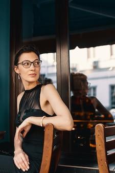 안경에 세련된 비즈니스 여성이 돌아서 카페에 앉아있는 동안 누군가를 보았습니다.