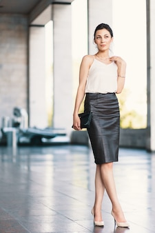 Refined businesswoman posing while wearing a leather pencil skirt