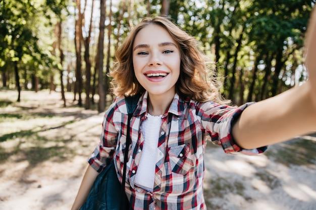 森の中を歩く市松模様のシャツを着た洗練された白人の女の子。晴れた日にselfieを作る笑う巻き毛の女性の屋外の肖像画。