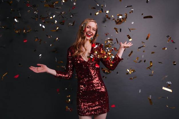 빨간 드레스 춤 파티에서 세련 된 백인 여자. 색종이 아래 포즈 귀여운 금발 여자의 스튜디오 샷.