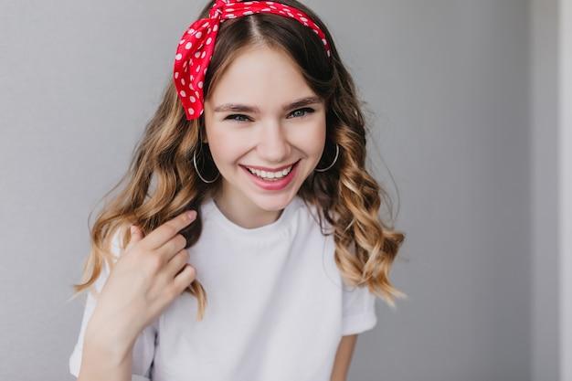 Raffinata ragazza caucasica ridendo. incredibile signora di buon umore con nastro rosso in posa.