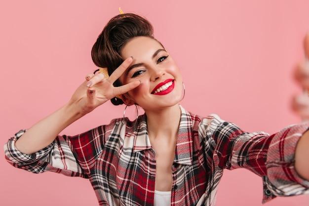 셀카를 복용 빈티지 복장에 세련된 백인 아가씨. 분홍색 배경에 평화 기호를 보여주는 웃는 핀 업 소녀.