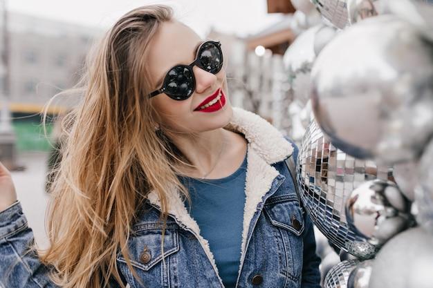 洗練された白人女性は、都会のストリートで笑顔のスタイリッシュな黒いサングラスをかけています。良い春の日にポーズをとるデニムジャケットの格好良いブルネットの少女の肖像画。