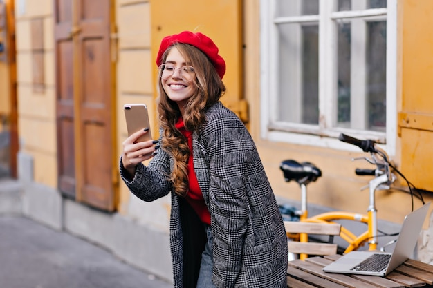 Raffinata ragazza francese riccia facendo selfie vicino a un tavolo di legno con il computer portatile su di esso