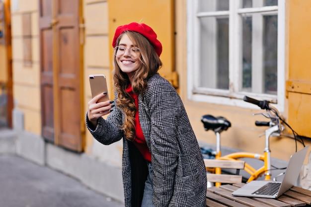 その上にラップトップと木製のテーブルの近くで自分撮りを作る洗練された巻き毛のフランスの女の子