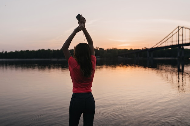 Raffinata ragazza europea in maglietta rosa che si rilassa dopo l'allenamento all'aperto. ritratto di donna affascinante che gode della vista dell'alba.
