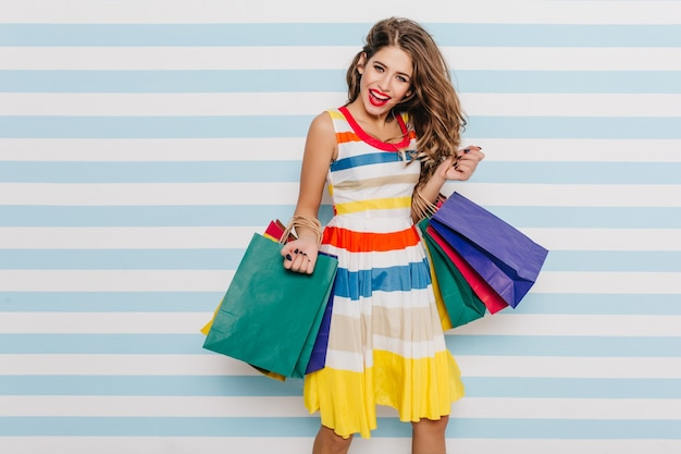 Утонченная европейская девушка со светло-каштановыми волосами развлекается после покупок. мечтательная барышня наслаждается продажами в бутике.