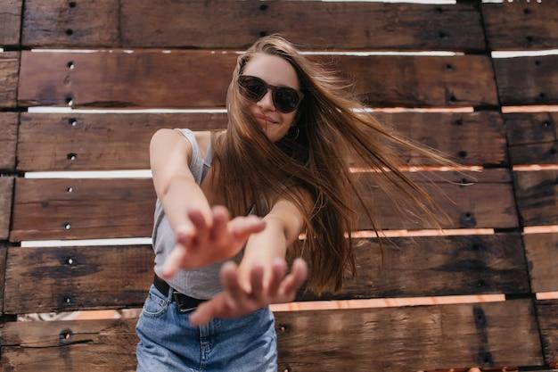 Утонченная европейская женщина в стильных солнечных очках танцует на деревянной стене. портрет изящной девушки с длинной прической, выражающей счастье в теплый летний день.