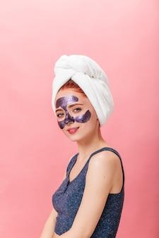 フェイスマスクでポーズをとる洗練されたヨーロッパの女性。頭にタオルを持った白人の女の子のスタジオショット。