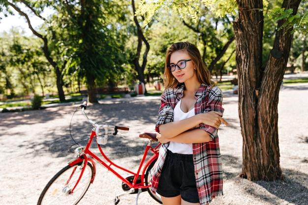 自転車に乗った後にポーズをとる眼鏡をかけた洗練された金髪の女性。赤い自転車とデボネアの女の子の屋外の肖像画。