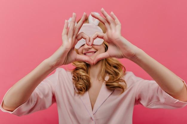朝に浮気しているskeepmaskの洗練された金髪の女性。ハートサインを作る夜のスーツで陽気な白人の女の子。
