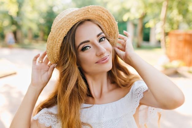 洗練された金髪の若い女性が優しく笑顔でヴィンテージの麦わら帽子を持っています。公園で喜んでポーズをとって気分の良いかわいい女の子のクローズアップの肖像画。