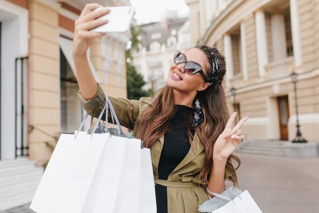 Raffinata fashionista donna divertirsi durante lo shopping e fare selfie