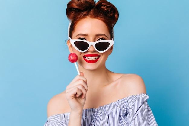 Donna raffinata dello zenzero che tiene caramelle dure e che ride. colpo dello studio della ragazza felice del pinup in occhiali da sole isolati sullo spazio blu.