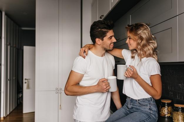 Raffinata ragazza che beve caffè con il marito. coppia rilassata agghiacciante in cucina mattina.