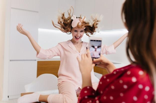 부엌에서 포즈를 취하는 동안 에너지를 표현하는 세련된 소녀. 빨간 옷에 갈색 머리 아가씨는 스마트 폰을 들고 분홍색 아이 마스크에 웃는 여동생의 사진을 찍습니다.
