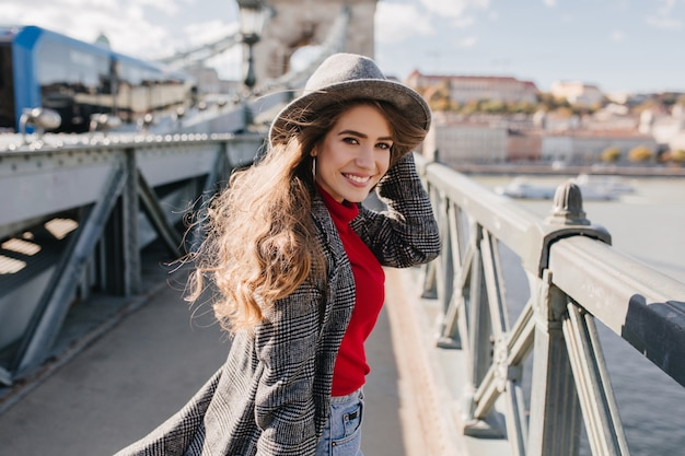 Утонченная девушка в элегантном твидовом пальто позирует с очаровательной улыбкой на городском фоне во время путешествия