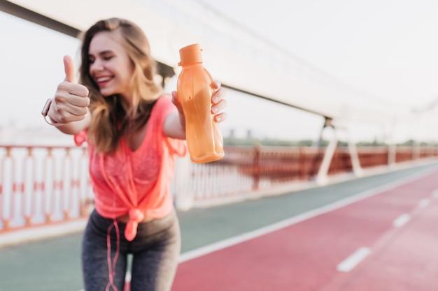 Утонченная девушка в серых спортивных штанах позирует с улыбкой. смеющаяся изящная женщина, стоящая с бутылкой на стадионе.