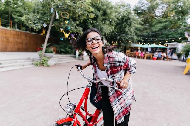 도시 주변을 타고 세련된 안경에 세련된 소녀. 나무 앞에서 자전거에 앉아 사랑스러운 검은 머리 여자의 야외 사진.