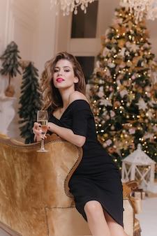 茶色のソファに座って興味を持って見ているトレンディな黒のドレスの洗練された女の子。元旦にゲストを待っている美しい若い女性の屋内写真。