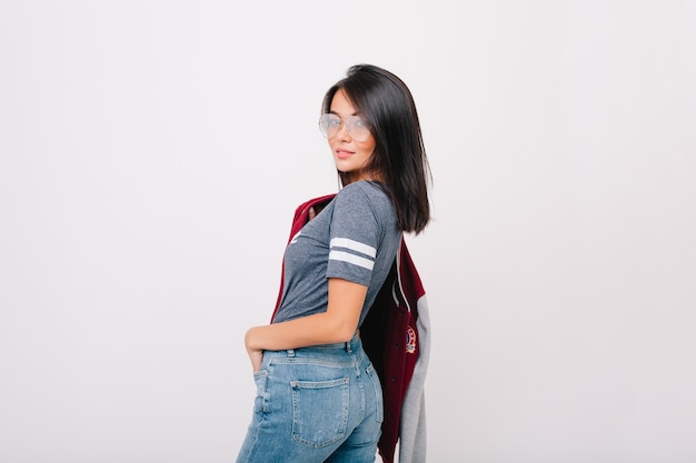 Refined girl with short black hair looking over shoulder, holding bomber in other hand. pretty lady with trendy haircut having fun and posing with pleasure in new glasses.
