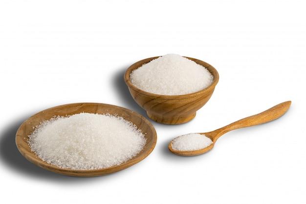 Рафинированный сахар-песок в деревянной миске, деревянной тарелке и в деревянной ложкой на белом фоне.