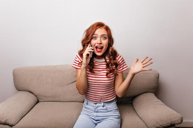 Утонченная дама с вьющейся прической разговаривает по телефону. симпатичная рыжая девушка сидит на диване и кому-то звонит.