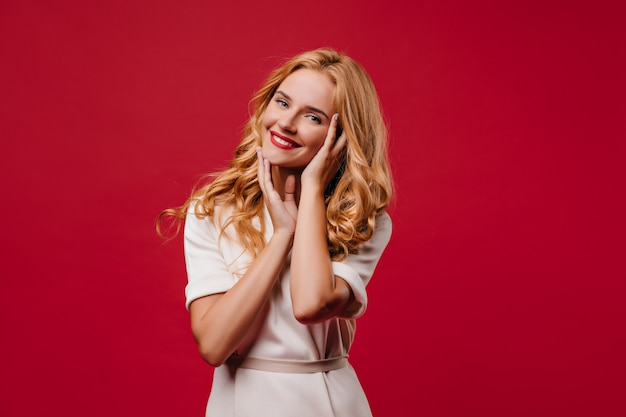 Raffinata ragazza dai capelli lunghi che tocca il suo viso con un sorriso. attraente donna bionda in piedi sulla parete rossa