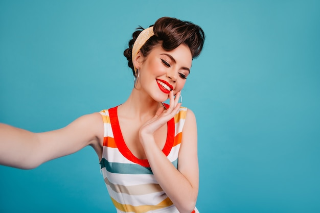 Refined pinup girl smiling with eyes closed. fashionable brunette young lady taking selfie on blue background.