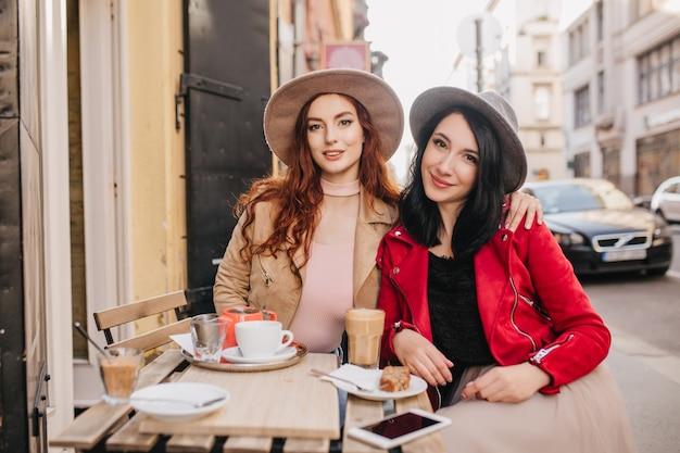 Изысканная рыжеволосая женщина обнимает подругу в кафе