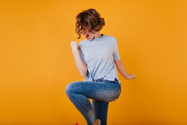 세련된 단발 여성이 점프하는 진한 파란색 청바지를 입는다.